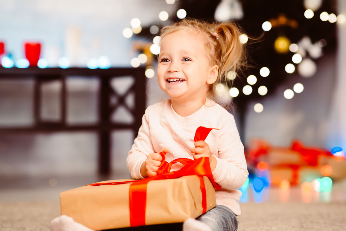 cute little girl with pigtails opens Christmas gift