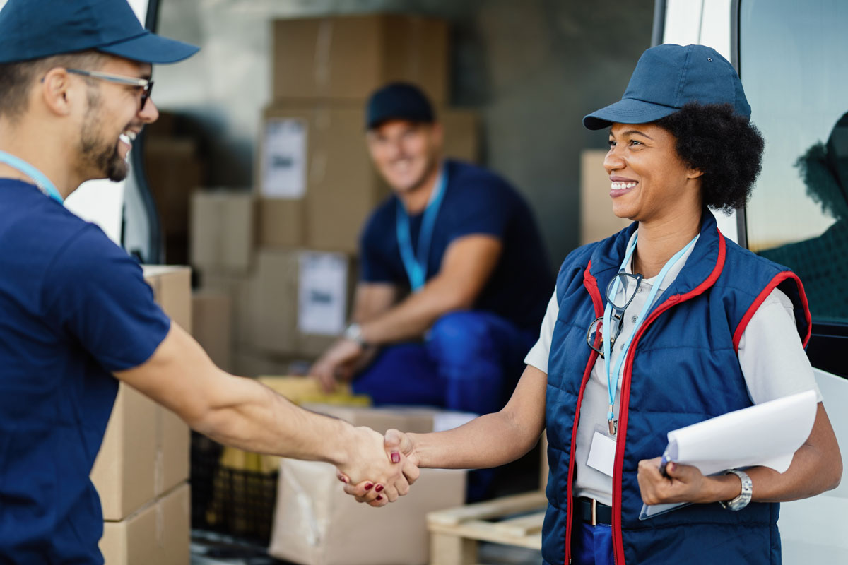 Delivery workers smiling while shaking hands.