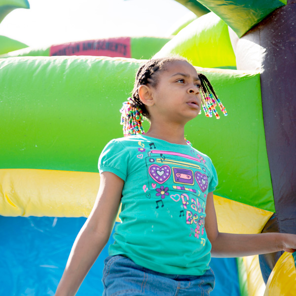 Young girl standing on a slide at a United Way Rock Hill, SC event.