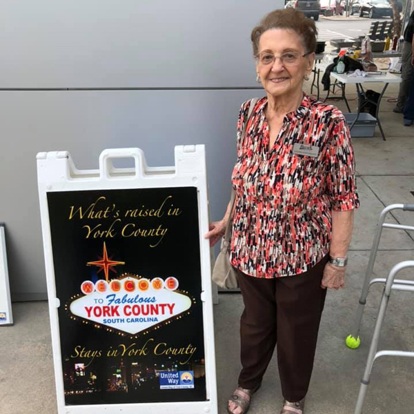 Older women standing in front of event sign for United Way