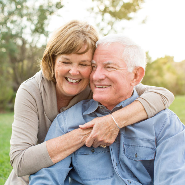 Older couple smiling together outside.