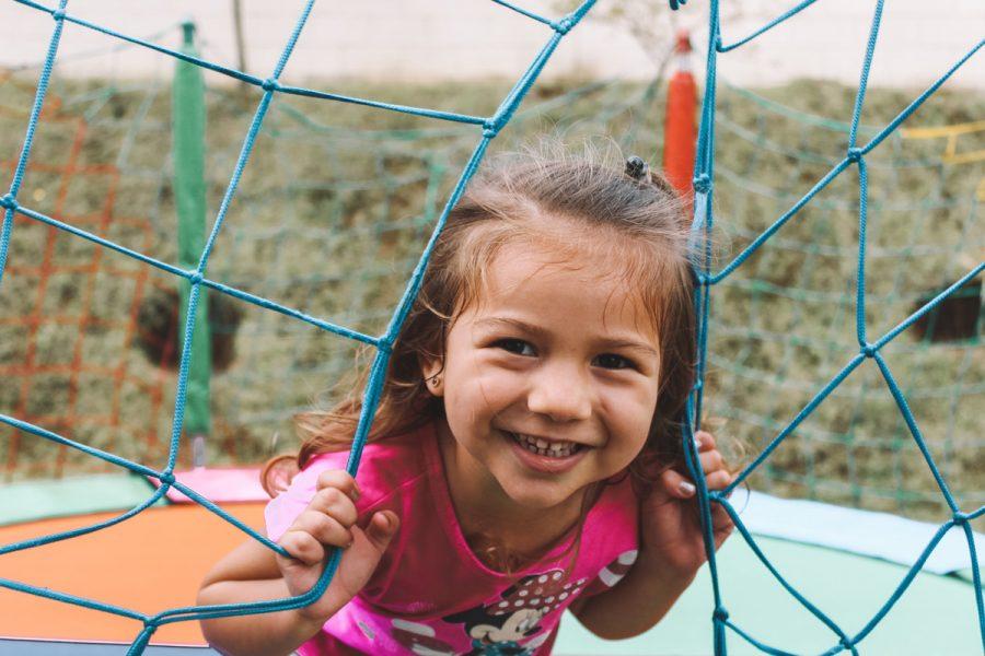 Little girl in pink shirt smiling outside.