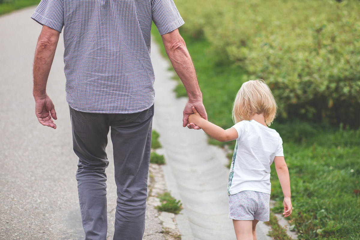 Older gentlemen holding hands with little girl while walking down the street.