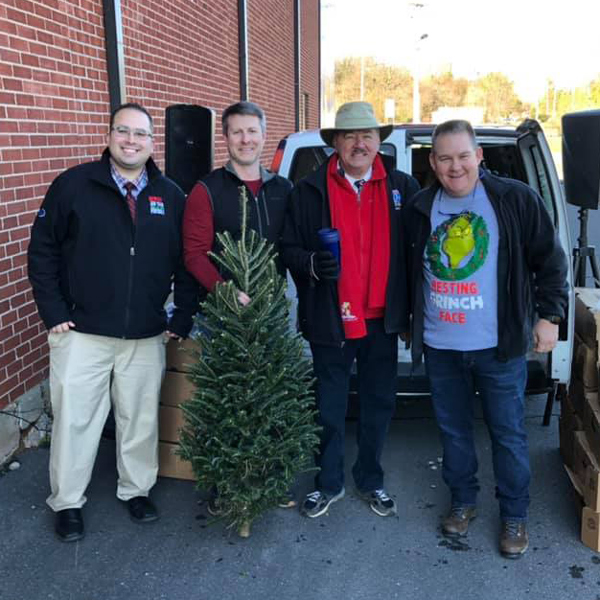Four men standing together with small Christmas tree
