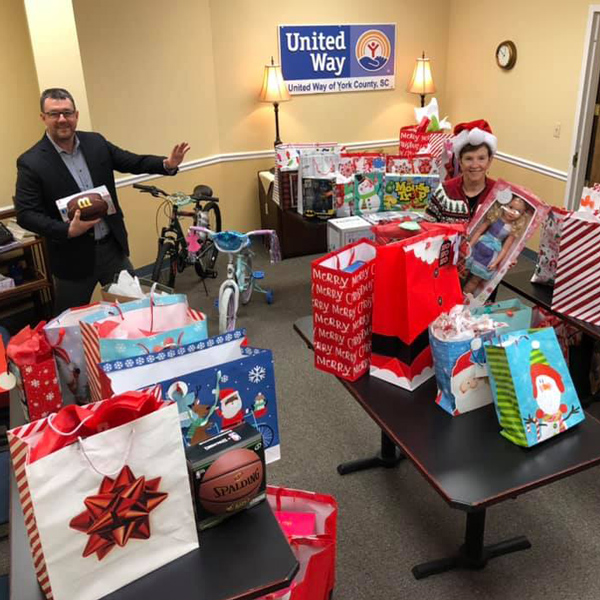 Man and women standing in a room full of presents donated by Family Trust Federal Credit Union