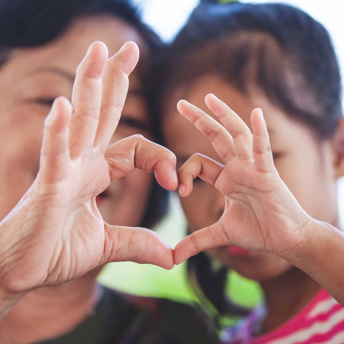 Mother and daughter holding up heart signs together.