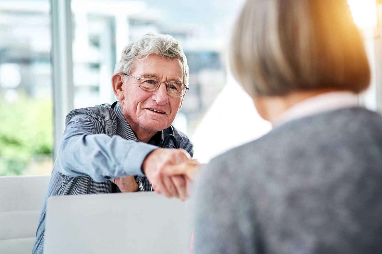 Older gentlemen shaking hands with women across a desk.