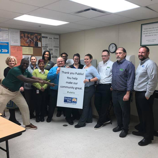 United Way employees and Publix employees standing together with a Thank you for contributing sign for Publix