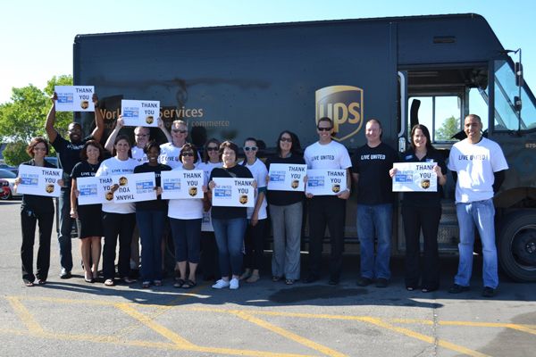 Group of UPS employees standing in front of UPS truck with thank you signs from United Way for partnering with them.