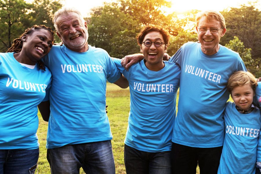 United Way volunteers in blue shirts smiling outside together.