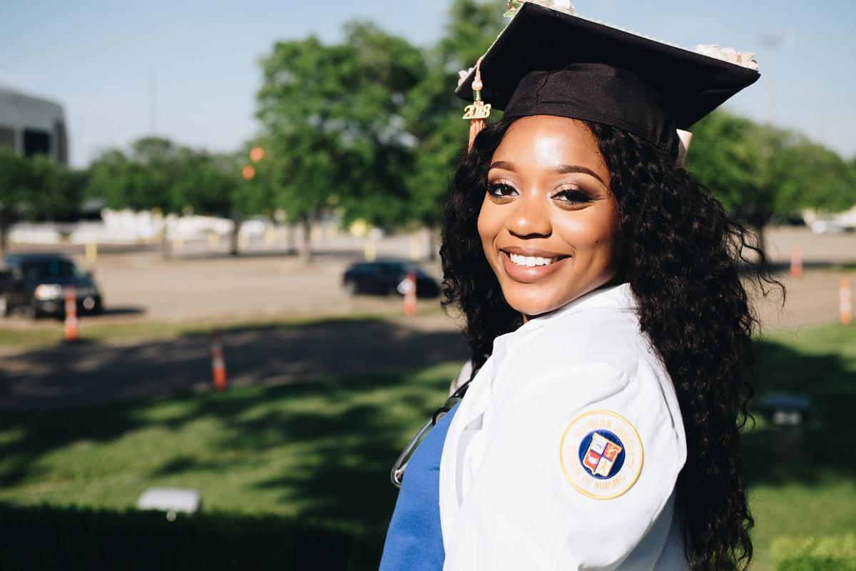 Young women wearing a graduation cap smiling outside.