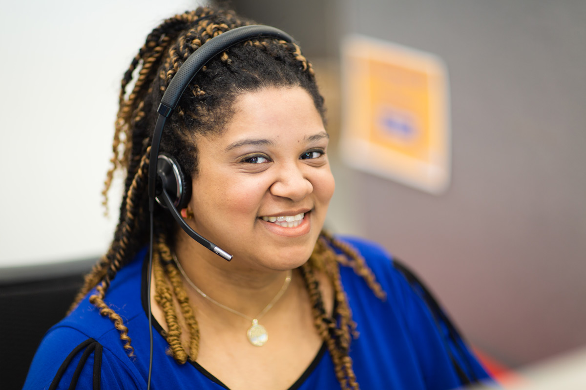 Women in blue shirt smiling with headset on.