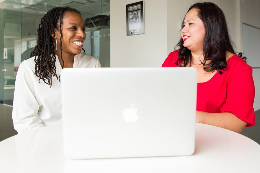 Two women with laptop discussing a workplace giving campaign with United Way